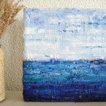 Schilderij lichtblauw - Kus van de zee II is een abstract klein schilderijtje met reliëf van 20 x 20 cm in (ultramarijn)blauw, turquoise, wit en oranje met stukjes juten, katoenen stof en zand erop.